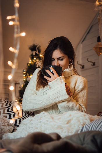 One Person Indoors  Young Adult Holding Hair Sitting Women Beauty Furniture Adult Looking Down Clothing Young Women Lifestyles Front View Long Hair Beautiful Woman Hairstyle Warm Clothing
