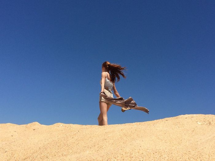 Low angle view of woman holding jacket against clear blue sky at desert