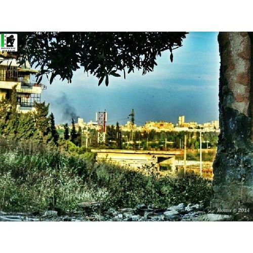 هناك حمص عندما كانت تحترق.. ذات قصف. التقطت الصورة من حي_الوعر أرشيف أثناء التقاط هذه القذيفة، كان القناص بالمرصاد، من يمين الشجرة هذه.