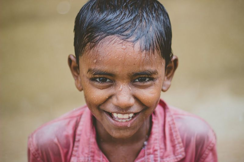 High angle portrait of smiling wet boy enjoying in rainy season