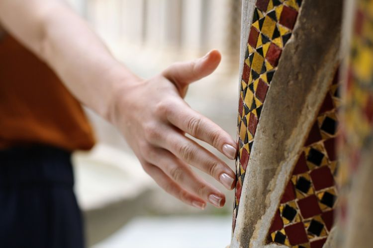 Close-up of hand touching pillar