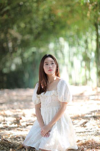 Portrait of woman sitting in park looking away
