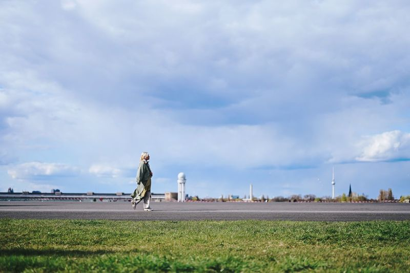 Side view of man standing on field against sky