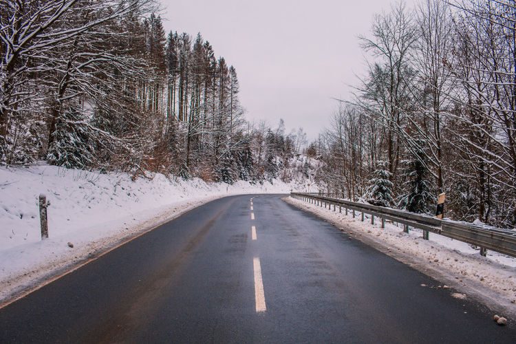 Road amidst bare trees against sky during winter