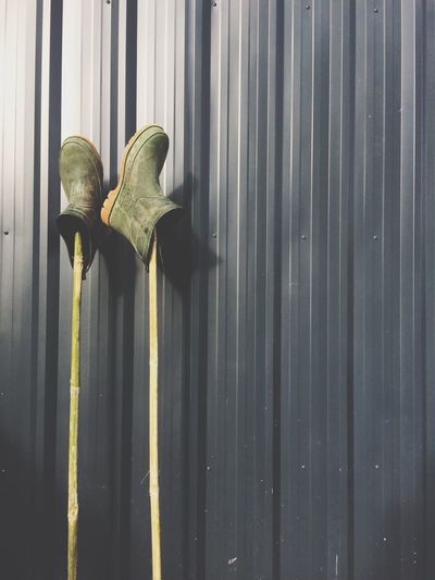 Close-up of pair of rubber boots on sticks leaning against fence