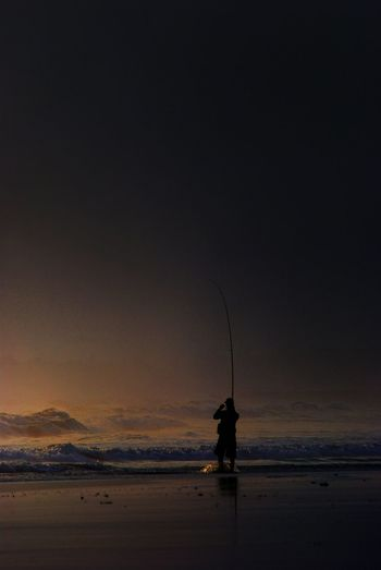 Silhouette Man Fishing At Sea Shore During Sunset