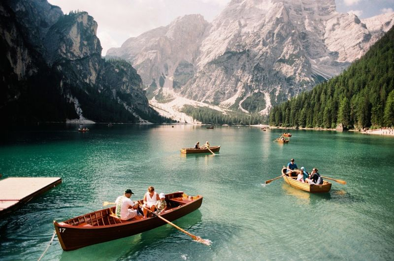 People on lake against mountains