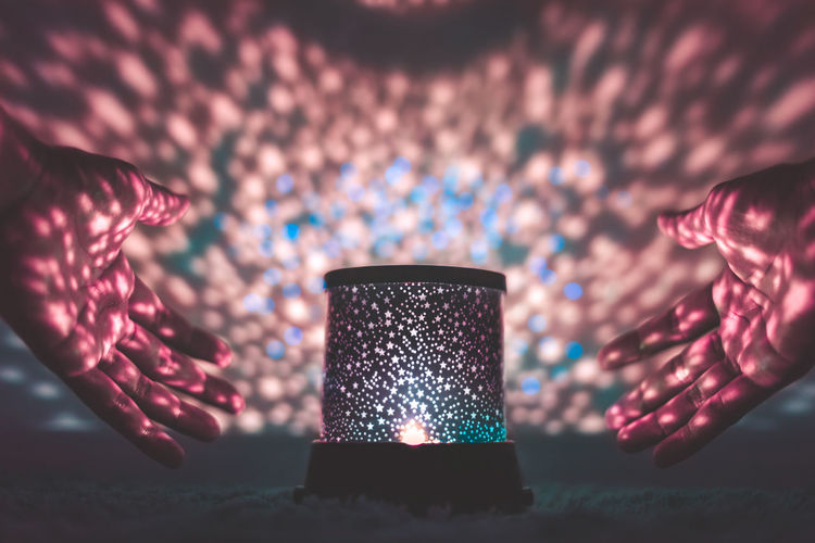 Close-up of hands around illuminated lantern