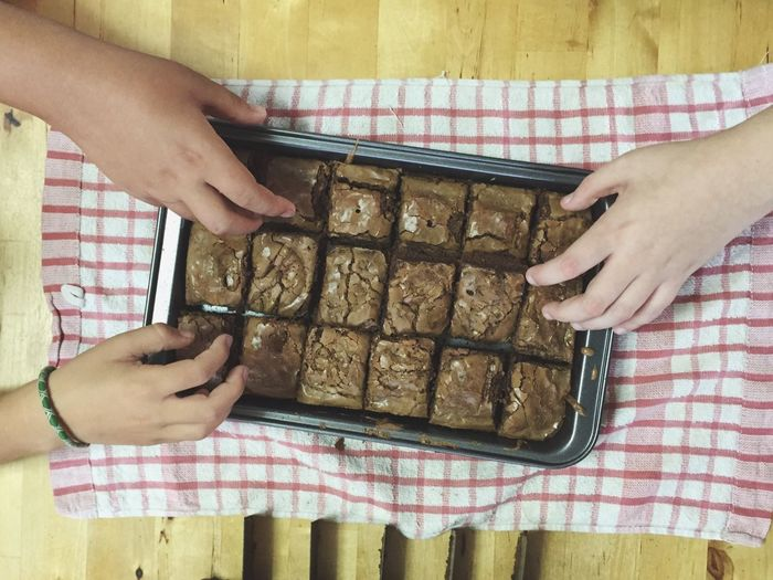 Cropped image of friends having brownies on table