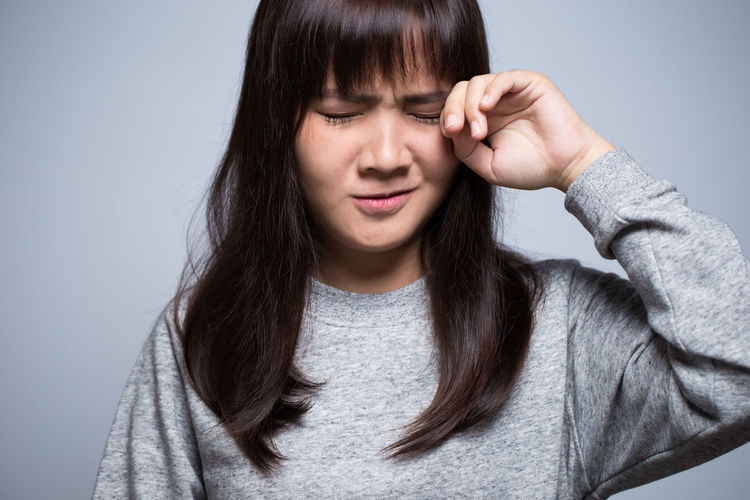 Sad Young Woman Against Gray Background