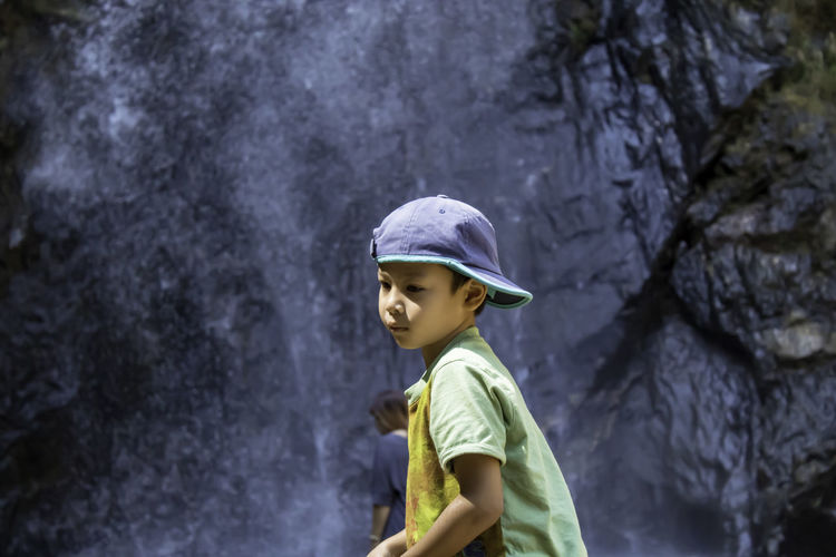 Boy looking away while standing against waterfall