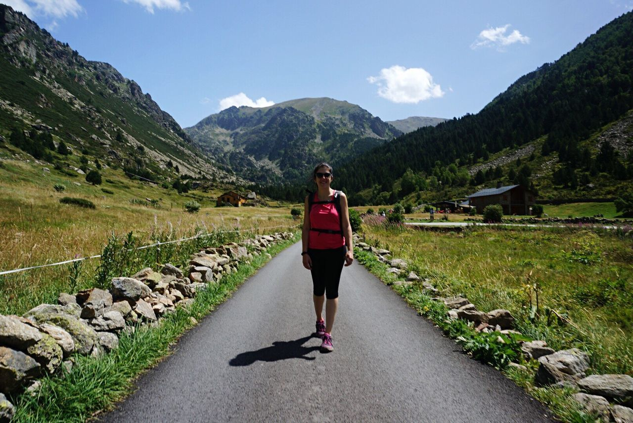 full length, real people, lifestyles, mountain, one person, healthy lifestyle, exercising, sports clothing, sky, nature, beauty in nature, young adult, leisure activity, jogging, young women, outdoors, day, standing, scenics, people