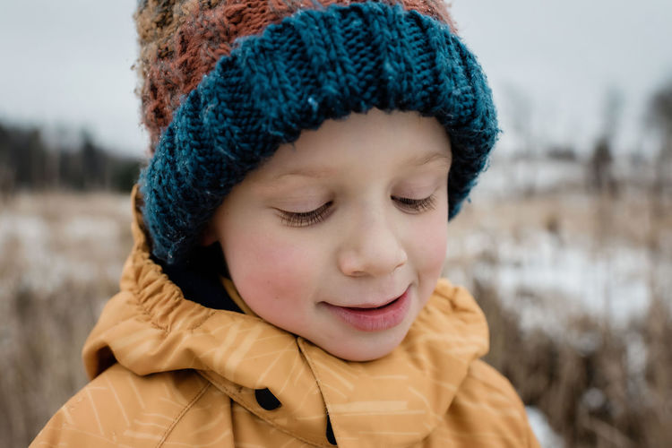 Close-up portrait of a boy in snow