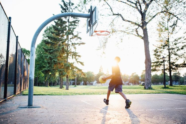 Man playing basket ball on field against sky