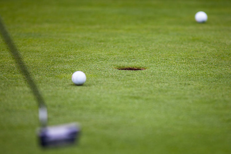 Close-Up Of Golf Club And Ball On Field