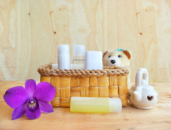 Close-up of toiletries and flower with teddy bear on table