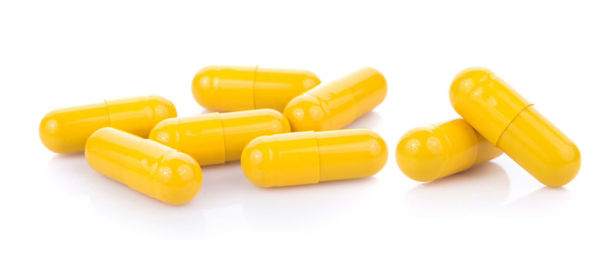 Panoramic view of yellow capsules over white background