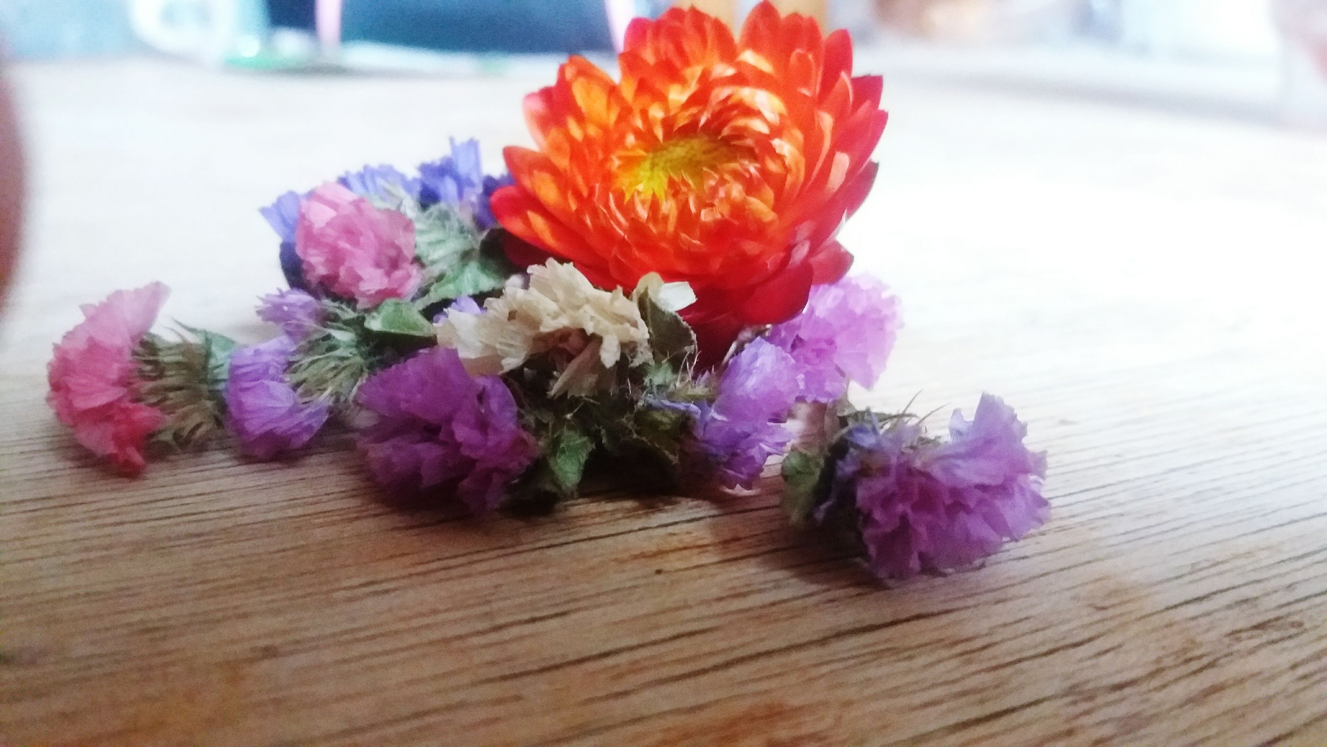 flower, petal, freshness, indoors, fragility, flower head, table, beauty in nature, close-up, wood - material, vase, still life, multi colored, bouquet, nature, bunch of flowers, no people, purple, flower arrangement, selective focus