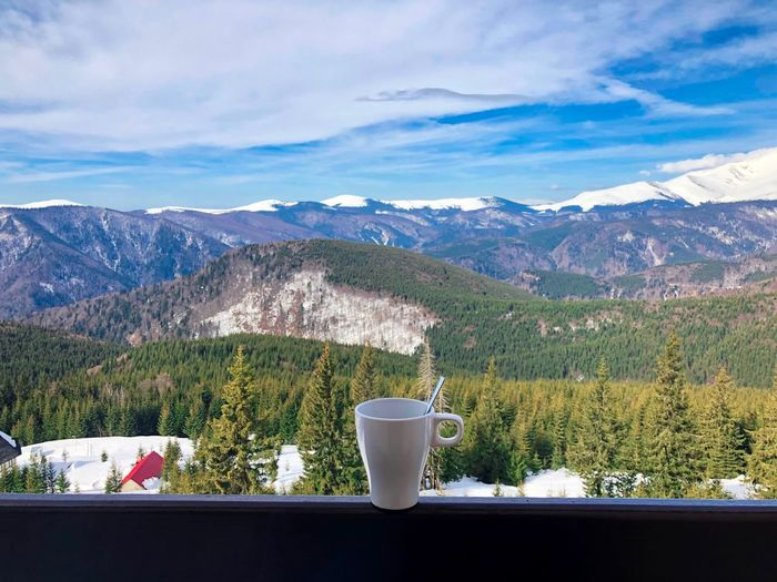 White cup placed on wooden railing on the balcony with view of snowcapped mountains Coniferous Tree Pine Tree Forest Trees Outdoors Day Railing Hotel Terrace Balcony Hot Drink Tea Beverage Cup Snowcapped Mountain Mountain Mountain Range Beauty In Nature Scenics - Nature Sky Cloud - Sky Mug Drink Coffee Architecture Nature Tranquility Idyllic Landscape No People