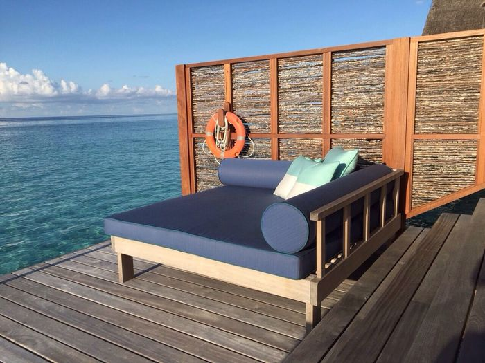Empty chaise longue on wooden dock by sea against sky