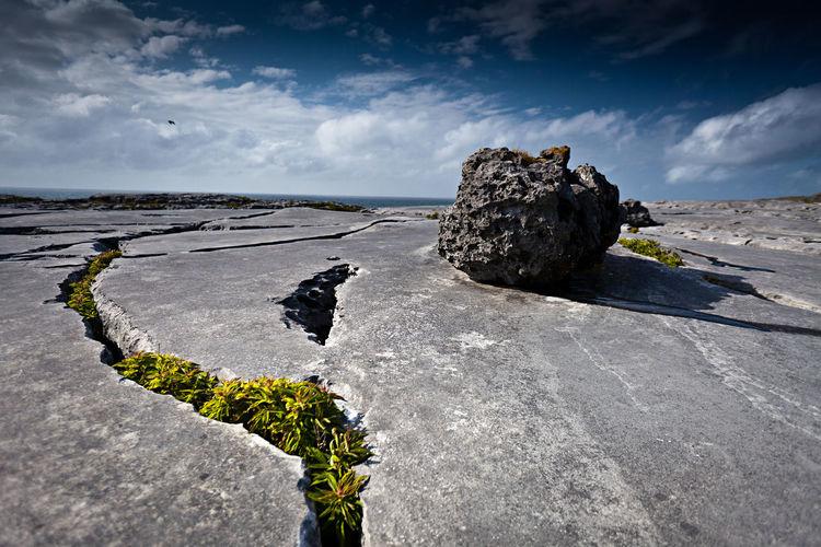 Rock on rocky field against sky