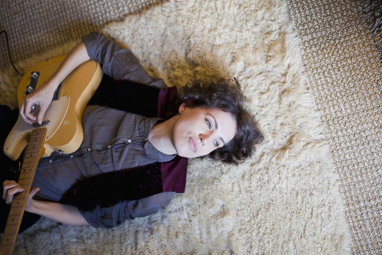 High angle portrait of smiling woman lying on floor