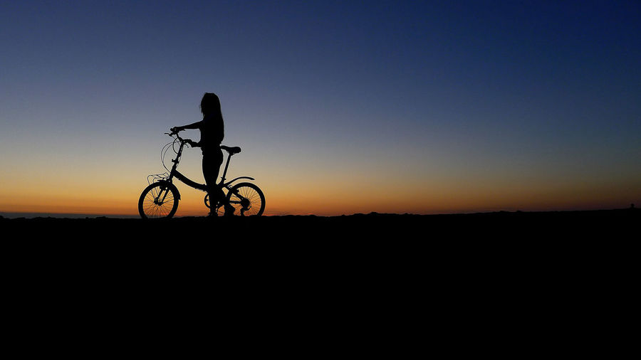 Silhouette person riding bicycle against clear sky during sunset