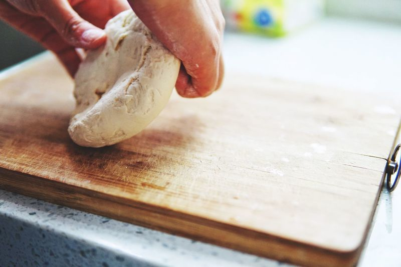 Close-Up Of Person Preparing Dough On Cutting Board