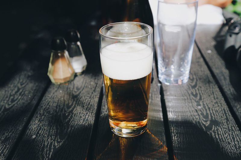 High angle view of beer glass on wooden table at restaurant