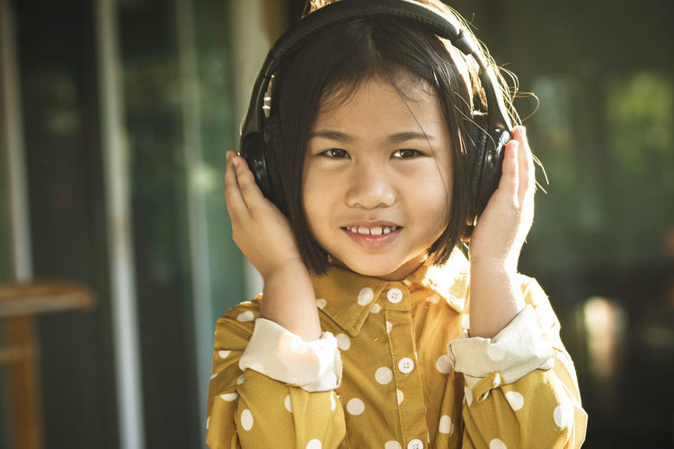 Portrait Of Smiling Cute Girl Listening To Music On Headphones