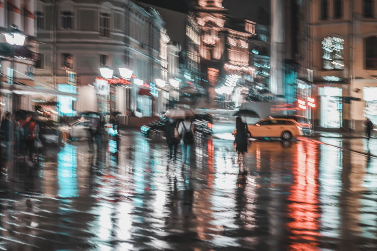 City street in rainy night, Abstract bright blurred background with unidentified people. Vivid illumination and reflection in wet pavement of shop windows and street lamps. Active lifestyle, leisure Illuminated City Night Motion Transportation Architecture Nightlife Rain Building Wet Road Car Street Land Vehicle Blurred Motion City Rainy Rain Blur Abstract Evening Bright People Reflection Lamps Pavement Umbrella