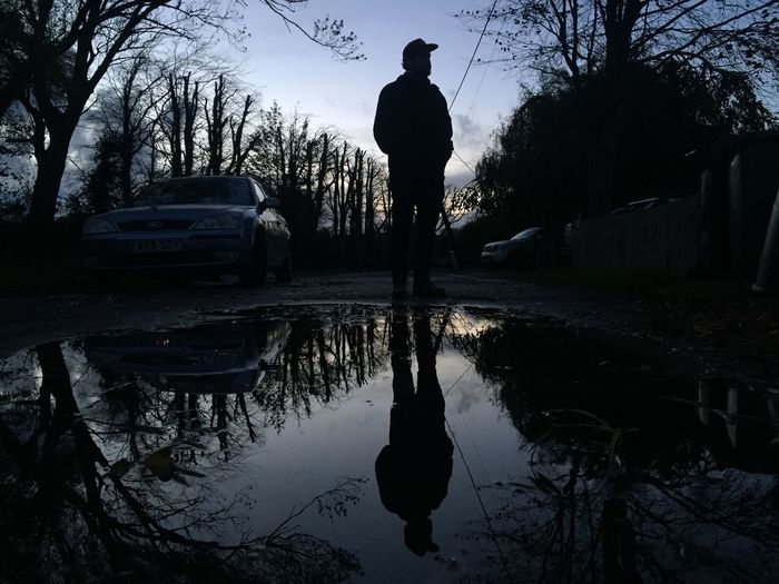 Rear view of silhouette man standing by lake against sky