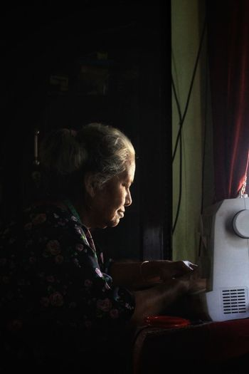 Side view of woman using mobile phone at home