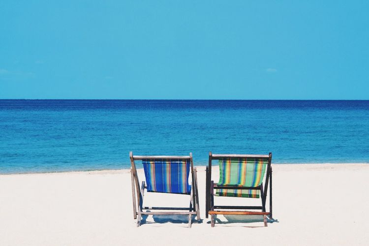 Deck chairs on beach against clear blue sky during sunny day