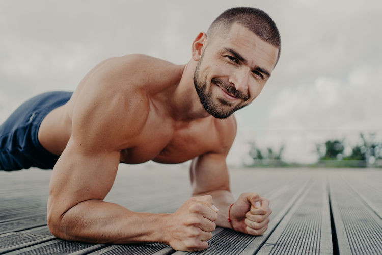 Portrait of shirtless young man exercising on wood