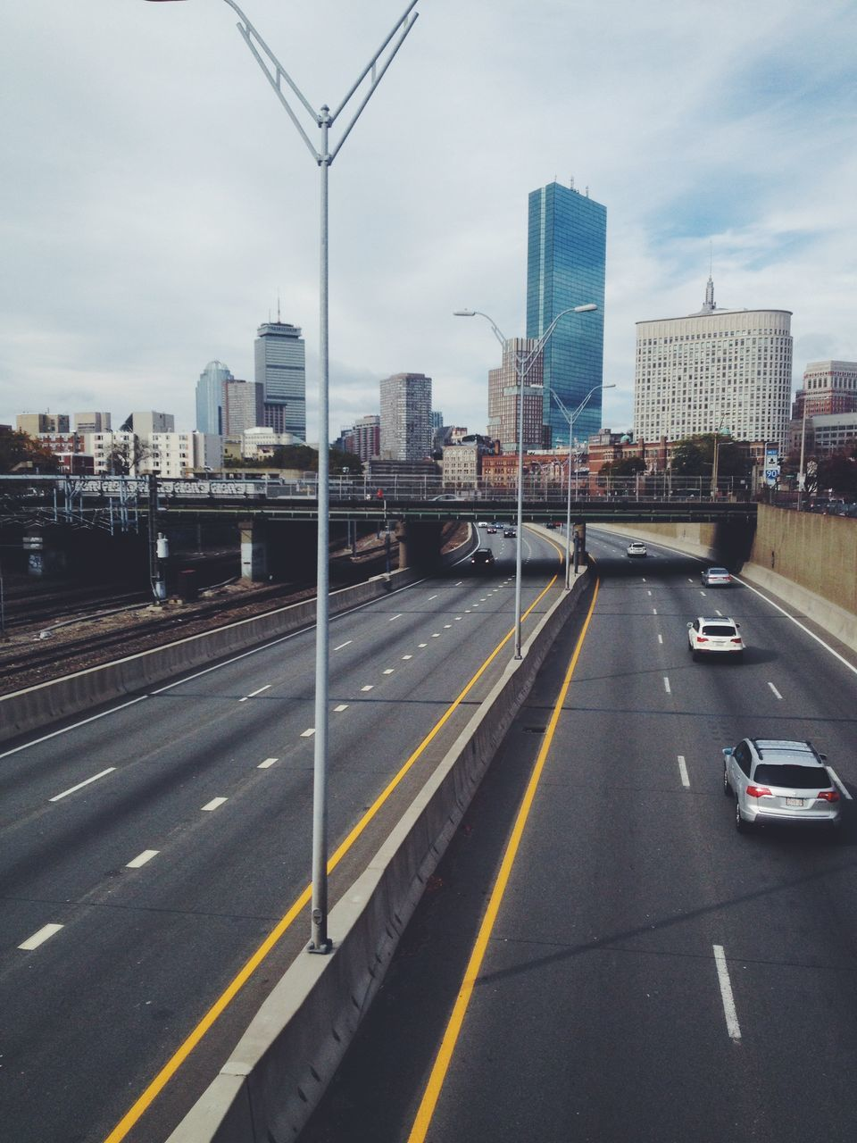 city, transportation, road, architecture, skyscraper, building exterior, car, built structure, sky, traffic, city life, cityscape, speed, travel destinations, mode of transport, outdoors, urban skyline, land vehicle, motion, tall, day, no people