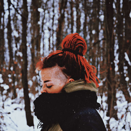 Portrait of woman in snow covered forest