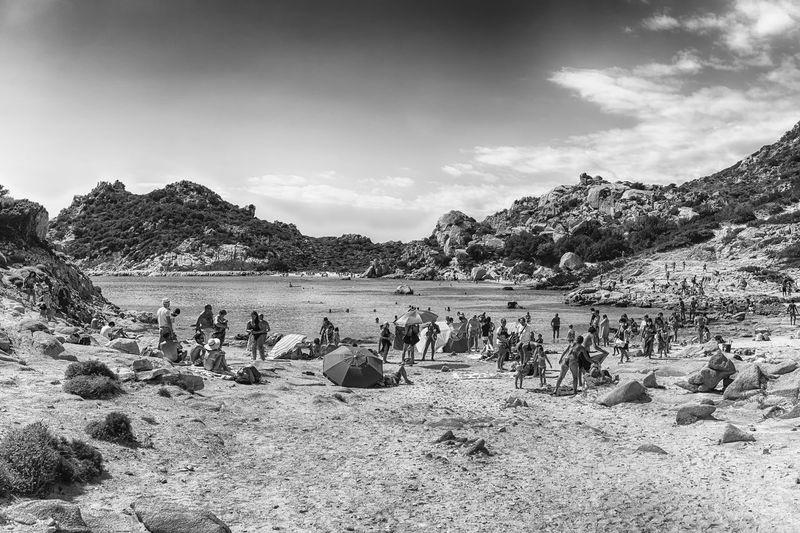 Group of people on rocks by beach against sky