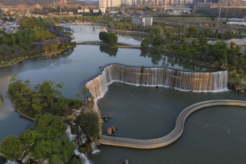 Kunming, China – May 17 ,2019: Aerial 360 degree view of the Kunming Waterfall Park at sunset, one of the largest manamde waterfalls in the world Kunming China Yunnan Waterfall Panlong Panglong Waterfall Park Sunset Drone  Aerial View Manmade Sunrise Water Lake Artificial Reservoir ASIA