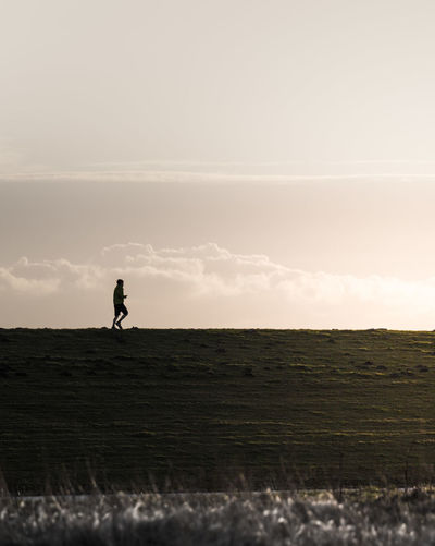 Man Running On Agricultural Field Against Sky
