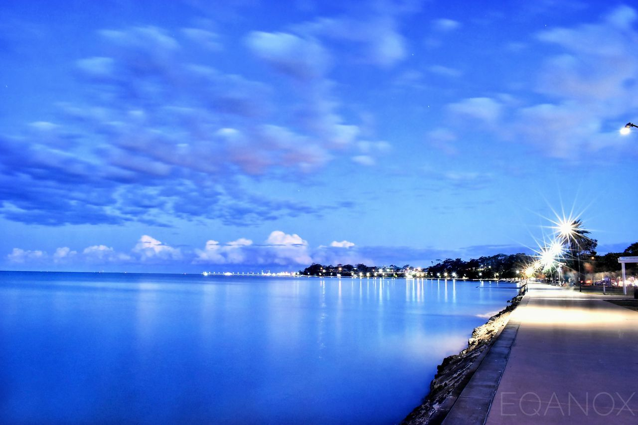 sky, water, reflection, scenics, tranquil scene, waterfront, illuminated, outdoors, night, nature, no people, cloud - sky, beauty in nature, tranquility, blue, tree, architecture