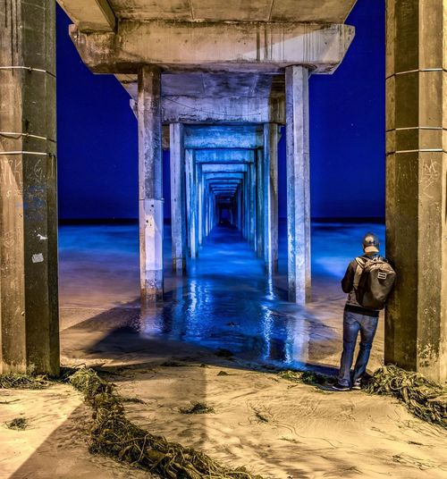 Underneath view of pier with man on beach