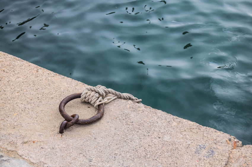 Iron Quayside Chain Close-up Concrete Day Docking Embankment High Angle View Iron Ring Metal Mooring Mooring Ring Nature Nautical Vessel No People Outdoors River Rope Rusty Sea Space For Text Strength Tied Up Water
