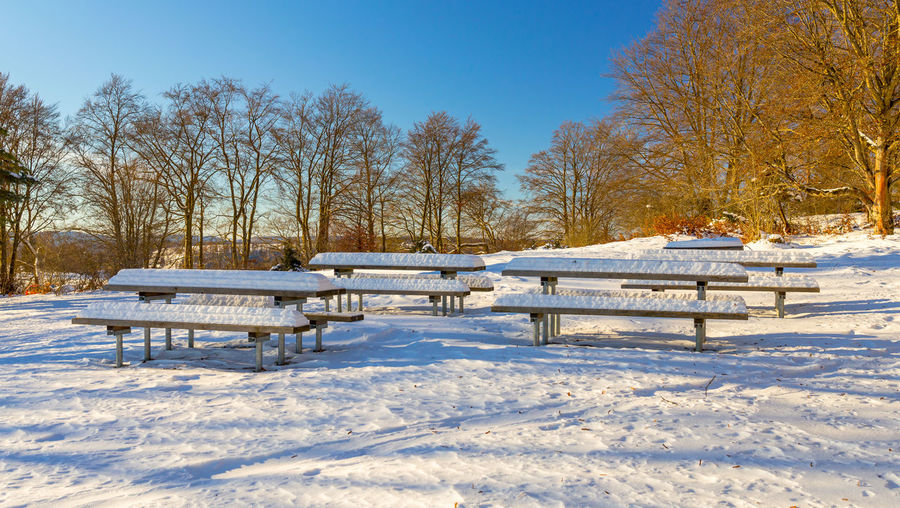Empty bench on snow covered field against sky