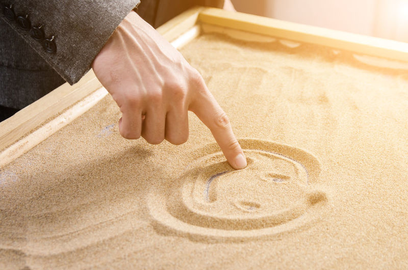 Midsection of person making smiley face on sand