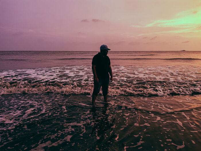 Rear view of man standing on beach during sunset