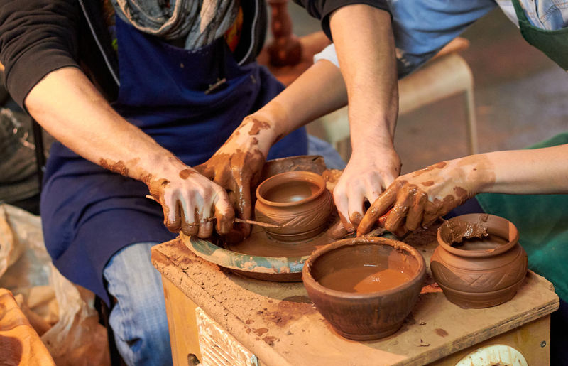 Midsection of people making pottery in workshop