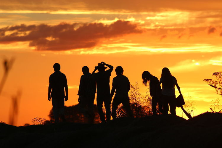 Beauty In Nature Friendship Full Length Leisure Activity Lifestyles Medium Group Of People Men Nature Orange Color Outdoors People Real People Silhouette Sky Standing Sunset Togetherness Women