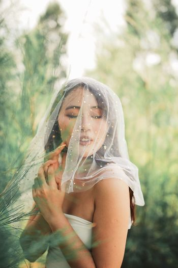 Woman holding veil while standing against trees