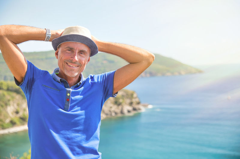 Portrait of smiling man standing against sea